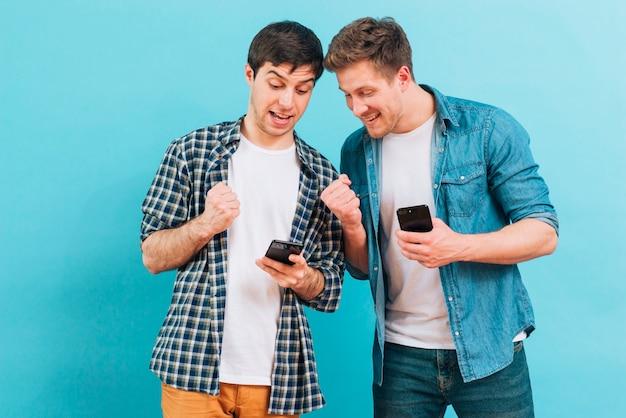 Dos amigos masculinos que aprietan su puño que mira el teléfono móvil contra fondo azul