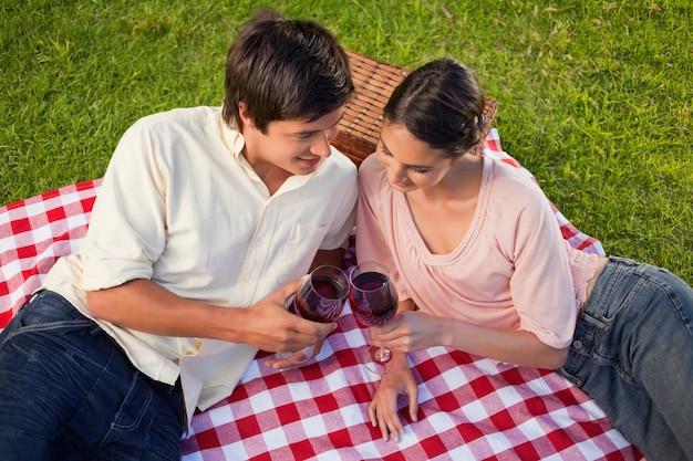 Dos amigos mirando hacia abajo mientras sostiene vasos de vino durante un picnic