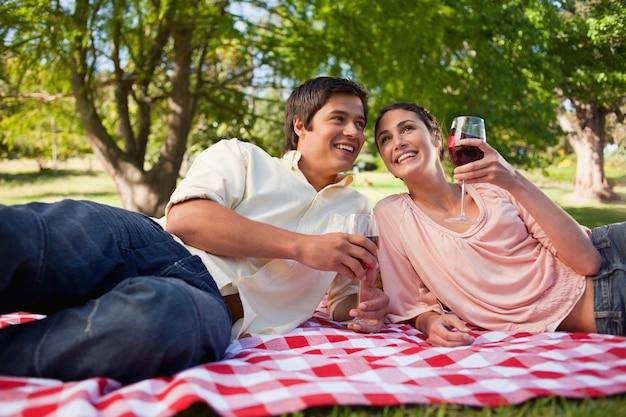 Dos amigos mirando a lo lejos mientras sostienen vasos durante un picnic