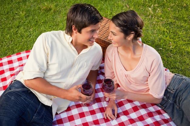 Dos amigos mirándose mientras sostiene vasos de vino durante un picnic
