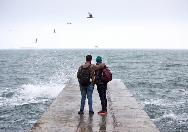 Dos amigos en el muelle, mirando el mar.