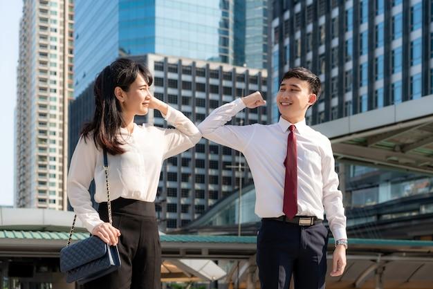 Dos amigos de negocios asiáticos se encuentran frente al edificio de oficinas saludando con un abrazo o un apretón de manos, en cambio se golpean los codos.