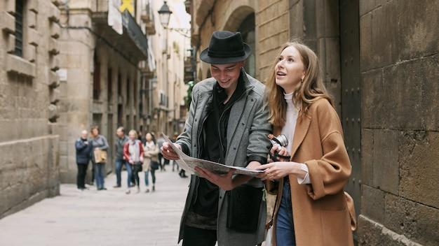 Dos amigos de pie en la calle y buscan algo usando un mapa.