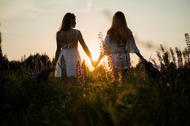Dos amigos de pie en el campo con ramos de flores de color púrpura