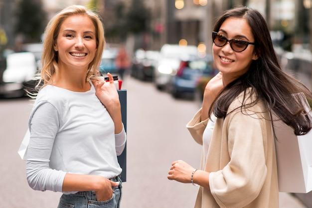 Dos amigos posando al aire libre mientras sostiene bolsas de la compra.