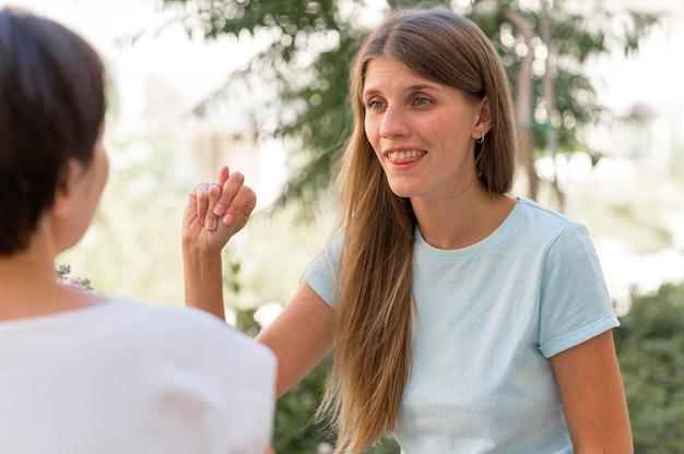 Dos amigos que se comunican entre sí mediante el lenguaje de señas.