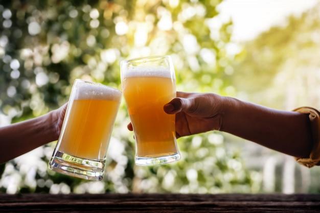 Dos amigos que hacen saludos con gafas y beben cerveza en el balcón en verano