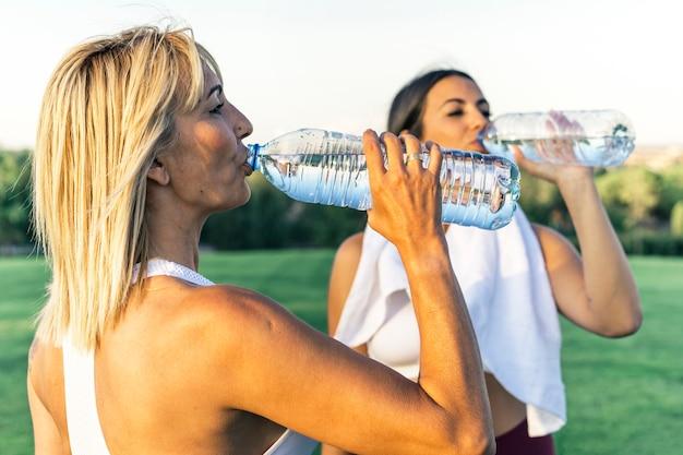 Dos amigos que son madre e hija, un joven y una persona mayor beben agua al aire libre después de correr y entrenar, vestidos con ropa deportiva y una toalla para el cuello y los hombros.