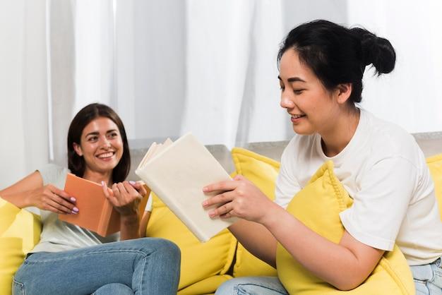 Dos amigos relajándose en casa en el sofá con libros