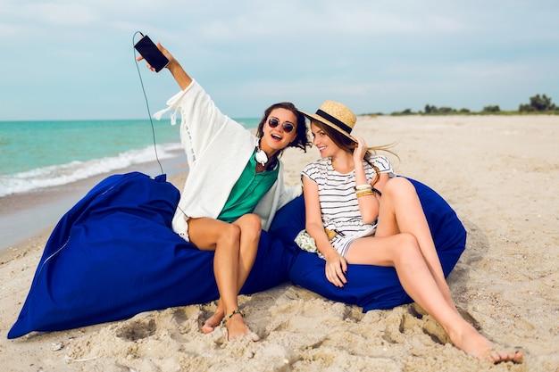 Dos amigos sentados en almohadas de playa, divirtiéndose