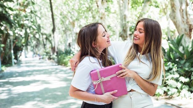 Dos amigos sonrientes con caja de regalo rosa mirando el uno al otro
