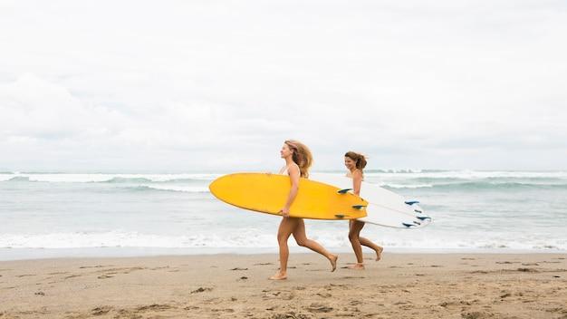 Dos amigos sonrientes corriendo en la playa con tablas de surf y espacio de copia