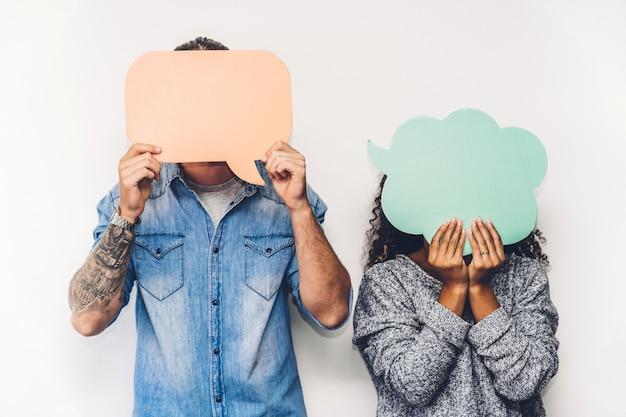 Dos amigos sosteniendo un icono de burbuja de diálogo juntos