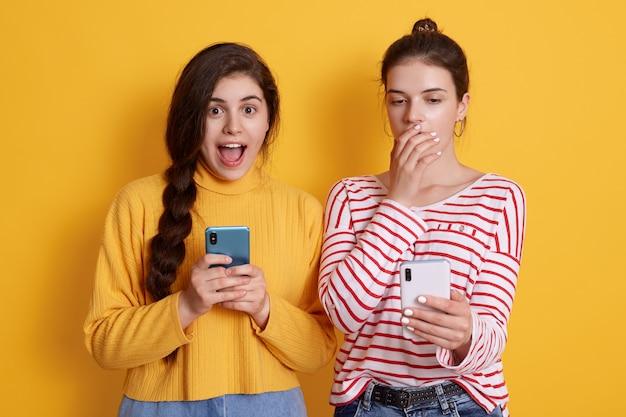 Dos amigos con teléfonos leyendo noticias impactantes en redes sociales