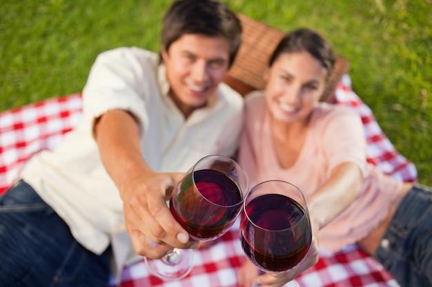 Dos amigos tocando sus gafas mientras se crían durante un picnic