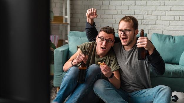 Dos amigos varones alegres viendo deportes en la televisión y tomando cerveza