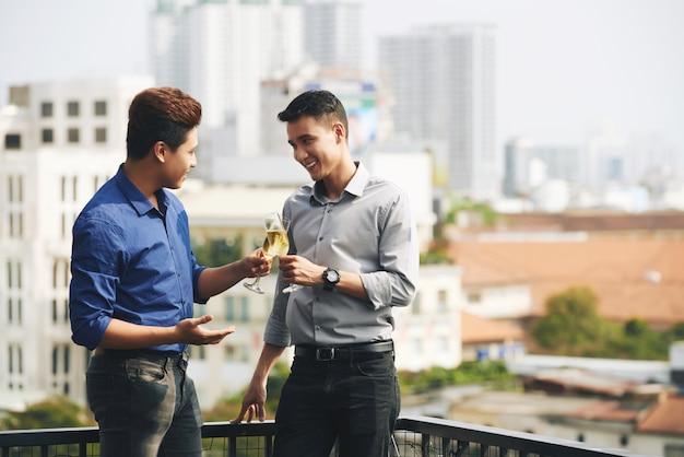 Dos amigos varones asiáticos charlando y disfrutando de champán en la fiesta urbana en la azotea