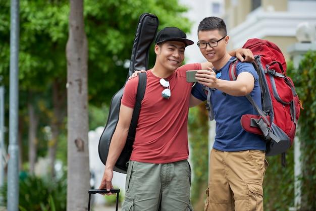 Dos amigos varones asiáticos con equipaje de pie en la calle de la ciudad, abrazándose y tomando selfie