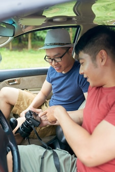 Dos amigos varones asiáticos sentados en el coche y revisando fotos en la cámara digital