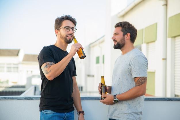 Dos amigos varones disfrutando de la fiesta, charlando, bebiendo cerveza