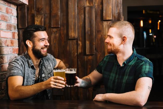 Dos amigos varones felices brindando anteojos alcohólicos en el bar