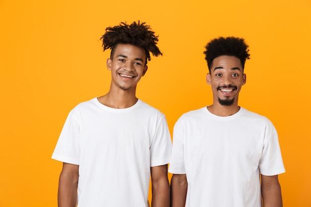 Dos amigos varones felices en camisetas de pie