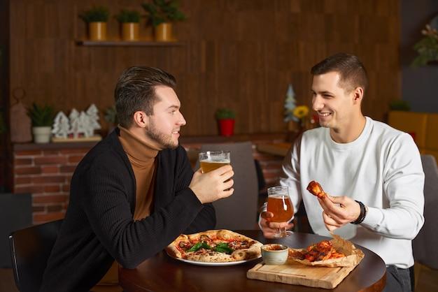 Dos amigos varones felices riendo y hablando con un vaso de cerveza en el pub local. hombres jóvenes relajantes, bebiendo deliciosa cerveza artesanal juntos en el bar. comunicación, estilo de vida, concepto de fin de semana.