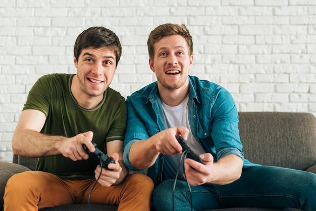Dos amigos varones felices sentados en el sofá jugando videojuegos con joysticks