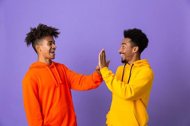 Dos amigos varones felices en sudaderas con capucha de colores
