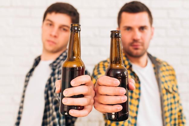 Dos amigos varones de pie contra la pared de ladrillo blanco que muestra botellas de cerveza hacia la cámara