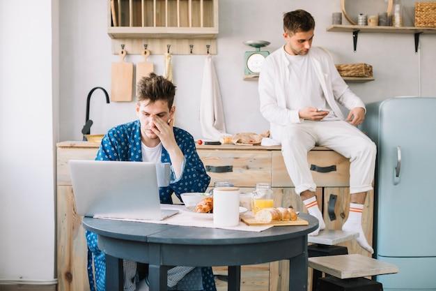 Dos amigos varones que usan una computadora portátil y un teléfono móvil en el momento de desayunar en la cocina