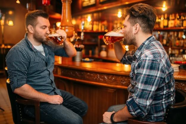Dos amigos varones sonrientes beben cerveza en el mostrador del pub.