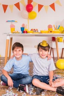 Dos amigos varones sonrientes sentados con confeti en el piso de madera dura