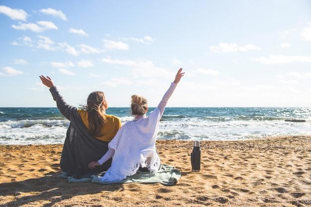 Dos amigos en viaje sentado junto al mar en la arena.