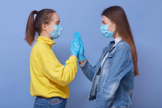 Dos amigos visten ropa casual, máscaras médicas y guantes de látex.