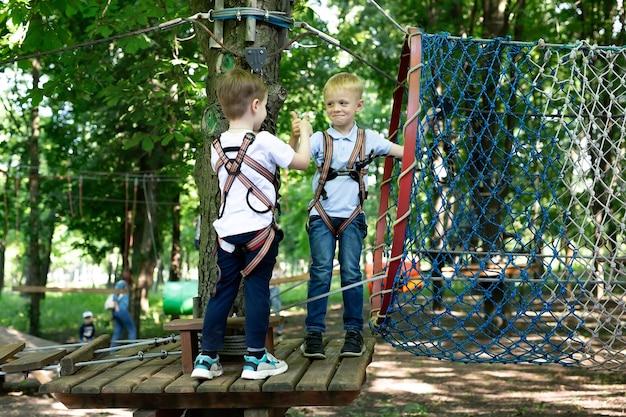 Dos amiguitos saludan mientras pasan las pruebas en el parque de cuerdas.