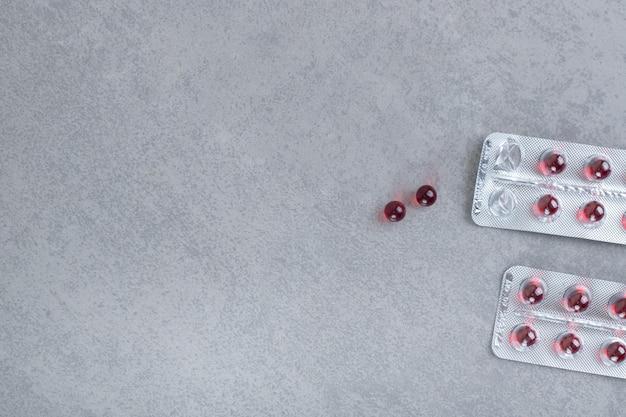 Dos ampollas con píldoras de círculo rojo sobre superficie gris