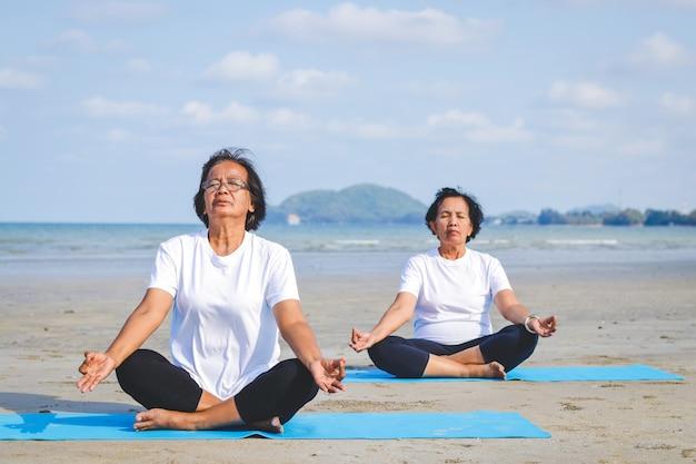 Dos ancianas haciendo ejercicio en la playa junto al mar sentados y haciendo yoga