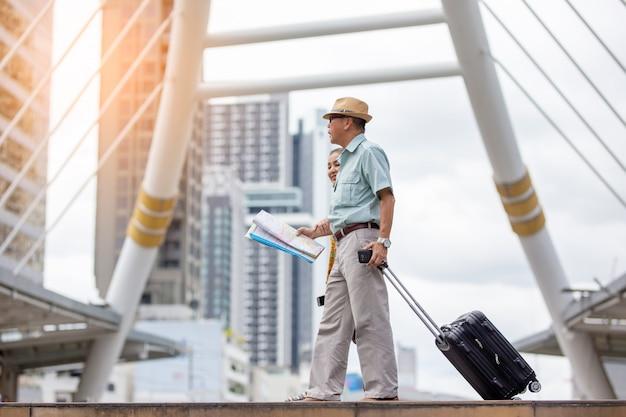 Dos ancianos asiáticos viajando con mapa y equipaje contra el edificio