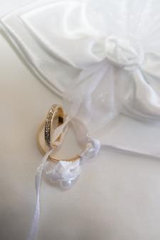 Dos anillos de boda dorados en cojín blanco matrimonio