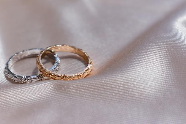 Dos anillos de boda de oro blanco y rosa sobre raso.