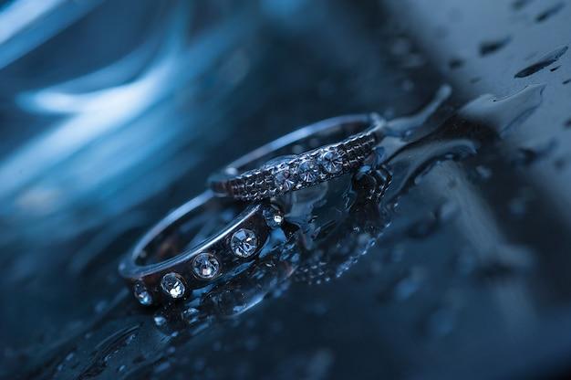 Dos anillos de boda sobre un fondo azul con gotas