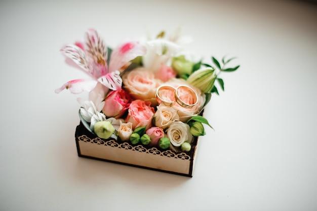 Dos anillos de bodas de oro dispuestos en la bonita composición de flores
