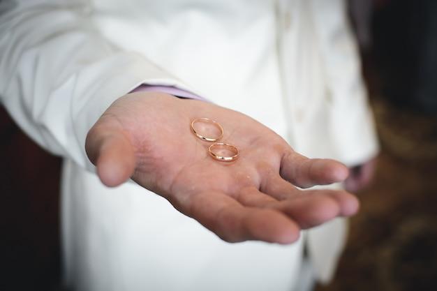 Dos anillos de bodas de oro se encuentran en la mano del hombre del novio.