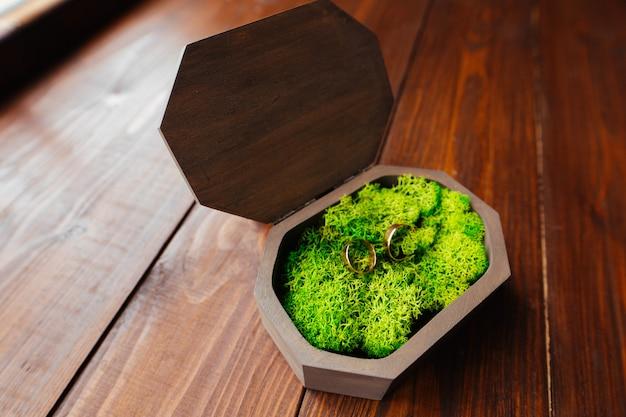 Dos anillos de bodas de oro en una hermosa caja de regalo en madera