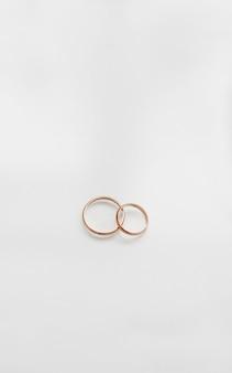 Dos anillos de bodas de oro sobre fondo blanco.
