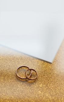 Dos anillos de bodas de oro sobre un fondo dorado.