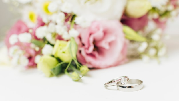 Dos anillos de bodas de plata cerca del ramo de flores.