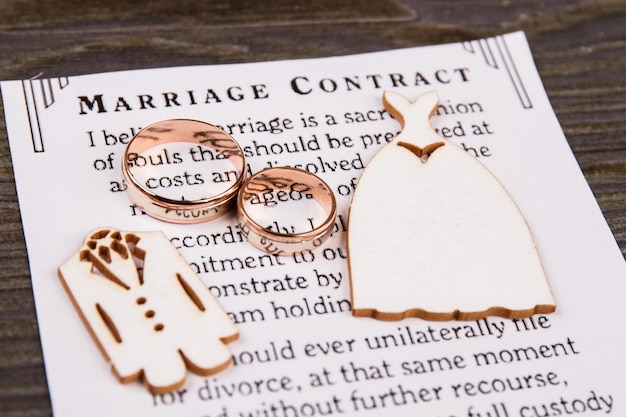 Dos anillos y contrato de matrimonio. primer plano de vestidos de novia de madera en miniatura.