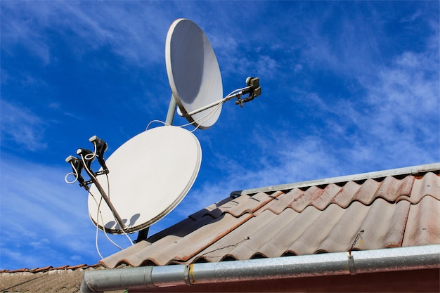 Dos antenas parabólicas blancas en el techo